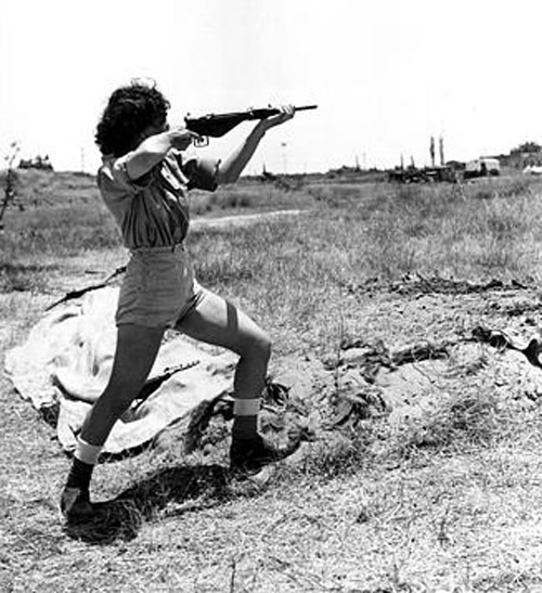 A female officer in charge of the range at the Hen women's corps camp near Tel Aviv, Palestine, gives a demonstration in the handling of a Sten gun on June 15, 1948 in the Arab-Israeli War.  Although non-combatants, members the new women's Army in Israel are taught to use guns for defense. (AP Photo/Public Domain)